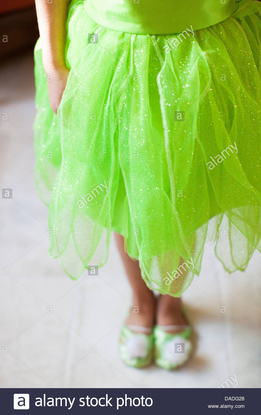 Lower half length shot of child in green fairy costume - Stock Image