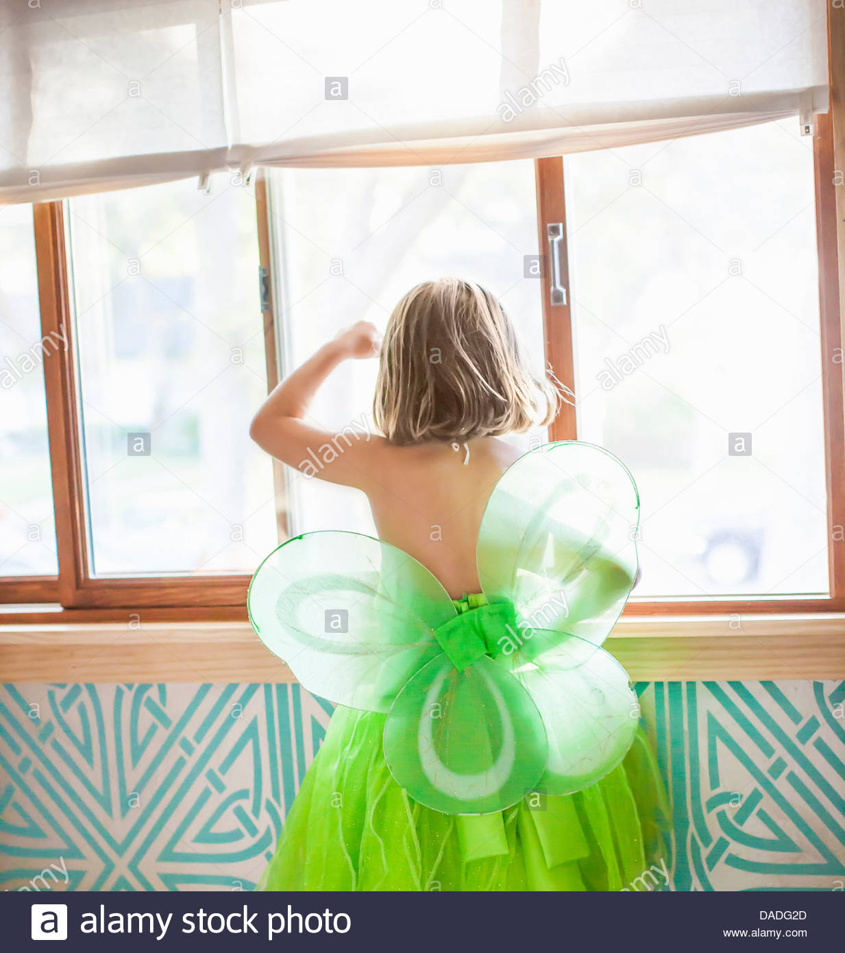 Back view of child in green fairy costume looking out window - Stock Image