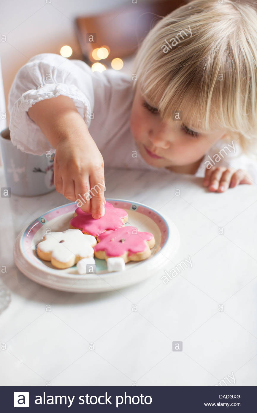 Girl taking cookie from plate - Stock Image