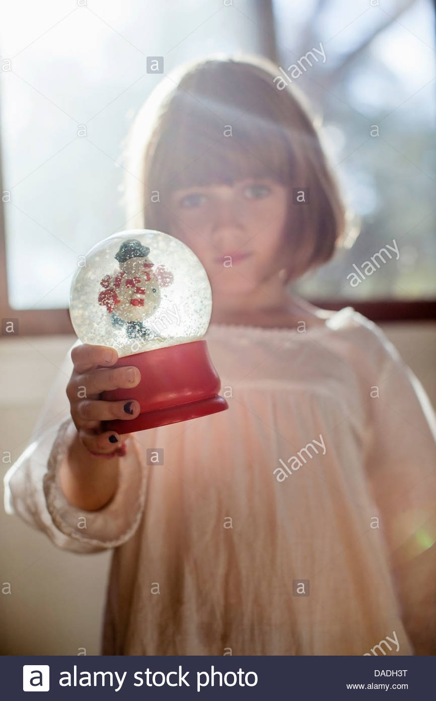 Girl playing with snow globe - Stock Image