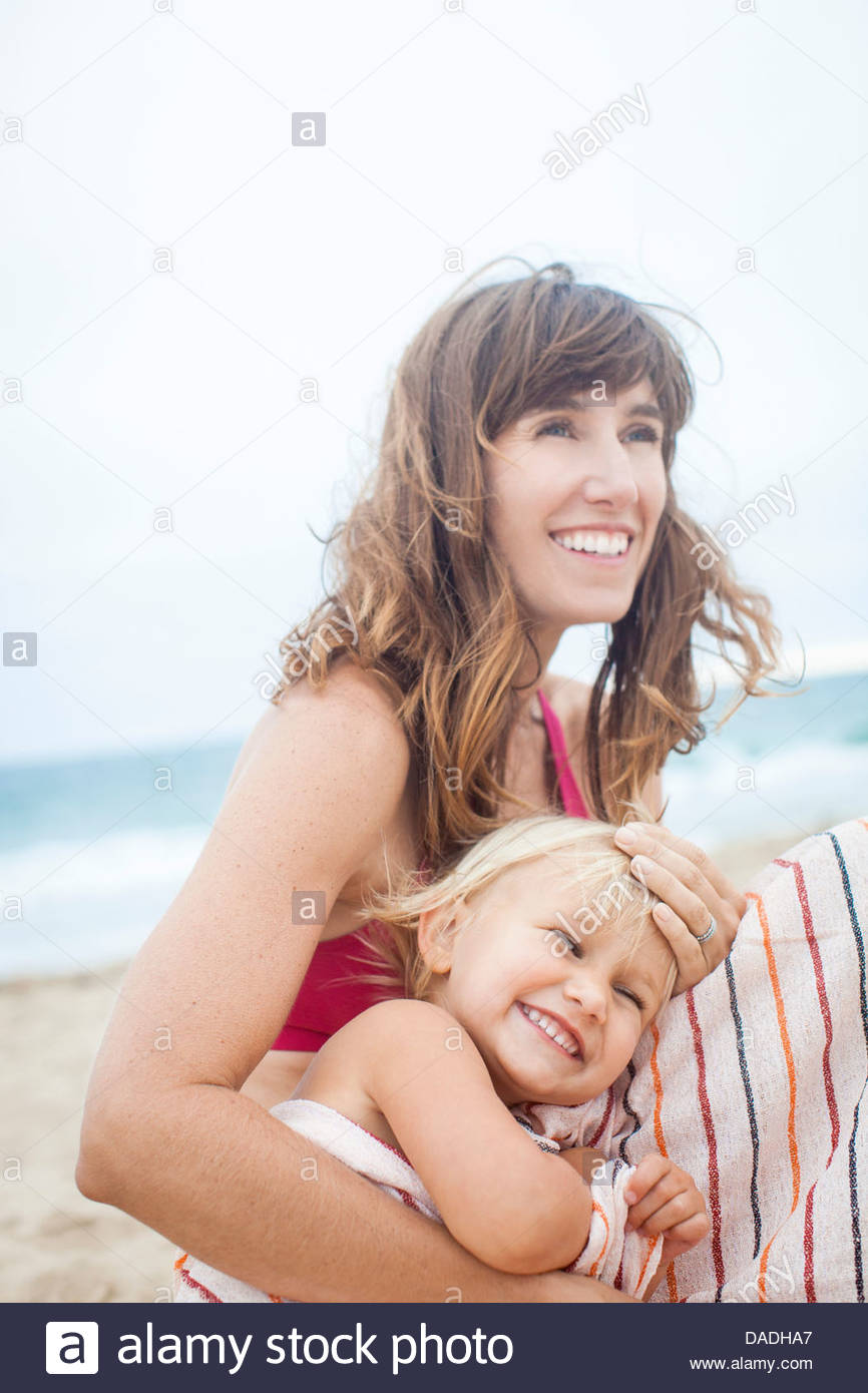 Mother and daughter laughing on beach - Stock Image