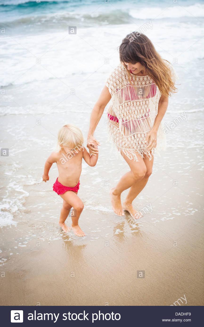Mother running with child out of the sea - Stock Image