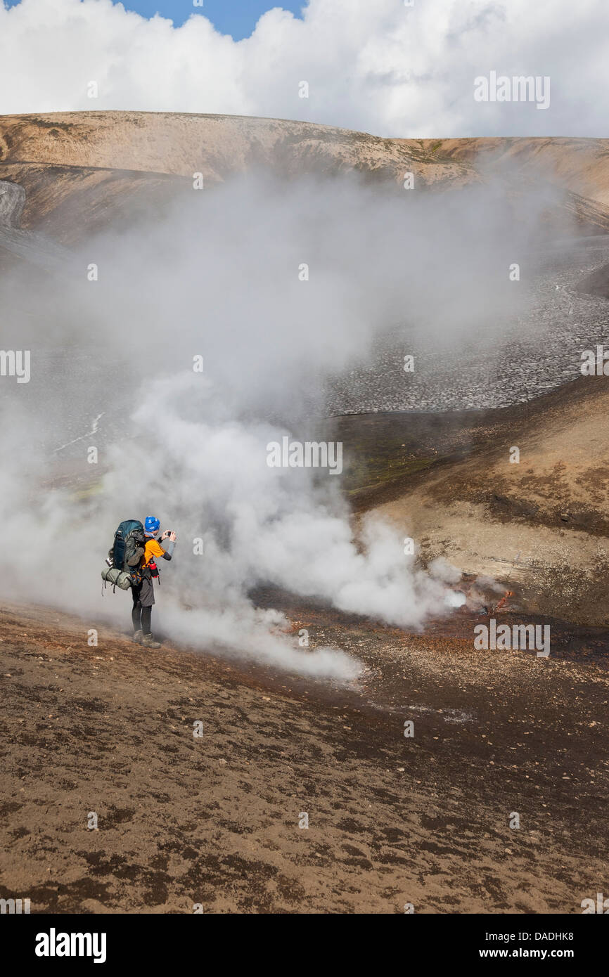 Hiker Photographing Steam Vents on the Laugavegur Hiking Trail Between Landmannalaugar and Thorsmork Iceland - Stock Image
