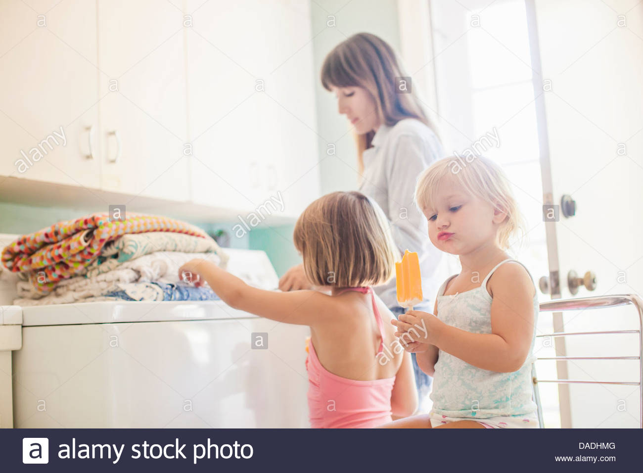 Mother and daughters in utility room with folded laundry - Stock Image