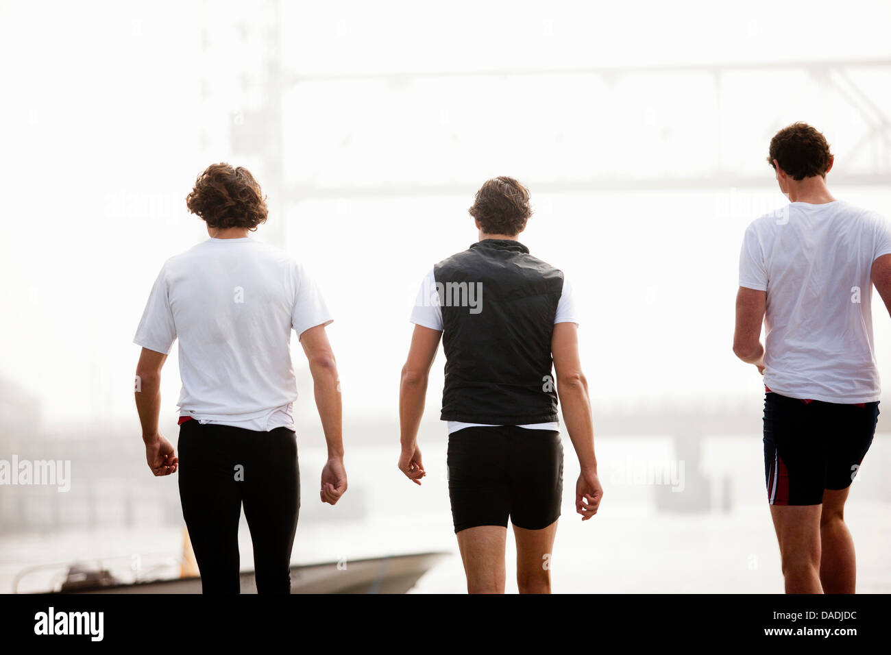 Back view of men walking to boat - Stock Image