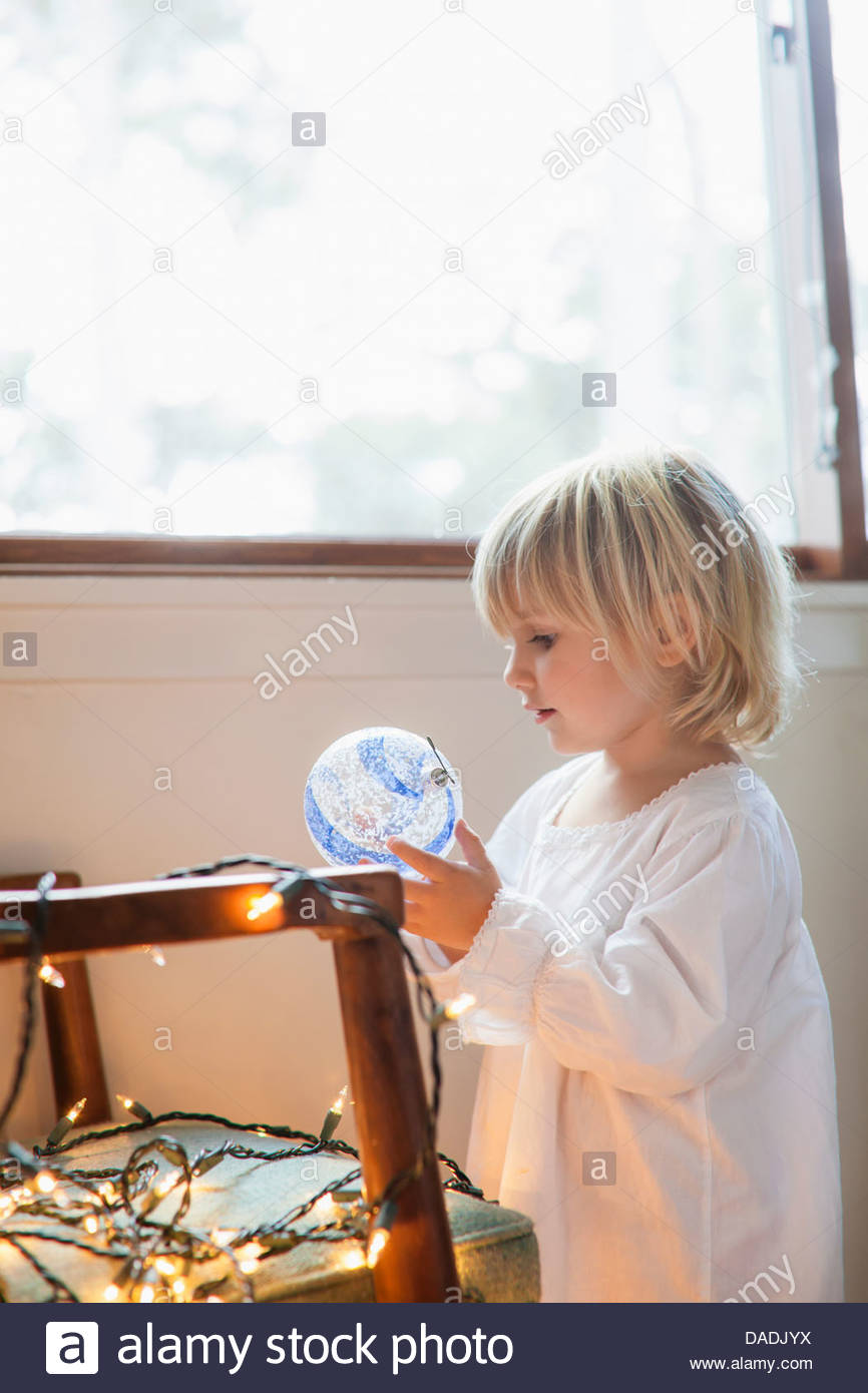 Girl looking at blue and white bauble - Stock Image