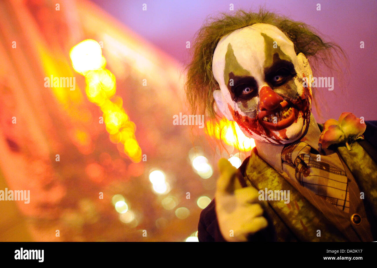 A performer costumed as zombie-clown scares visitors of the MoviePark in Bottrop, Germany, 27 October 2011. With - Stock Image