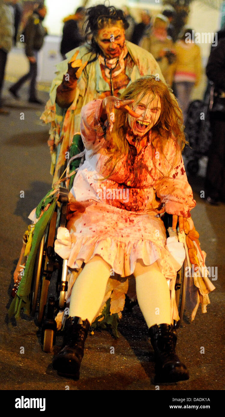 Two performers costumed as monsters scare visitors of the MoviePark in Bottrop, Germany, 27 October 2011. With Christmas - Stock Image