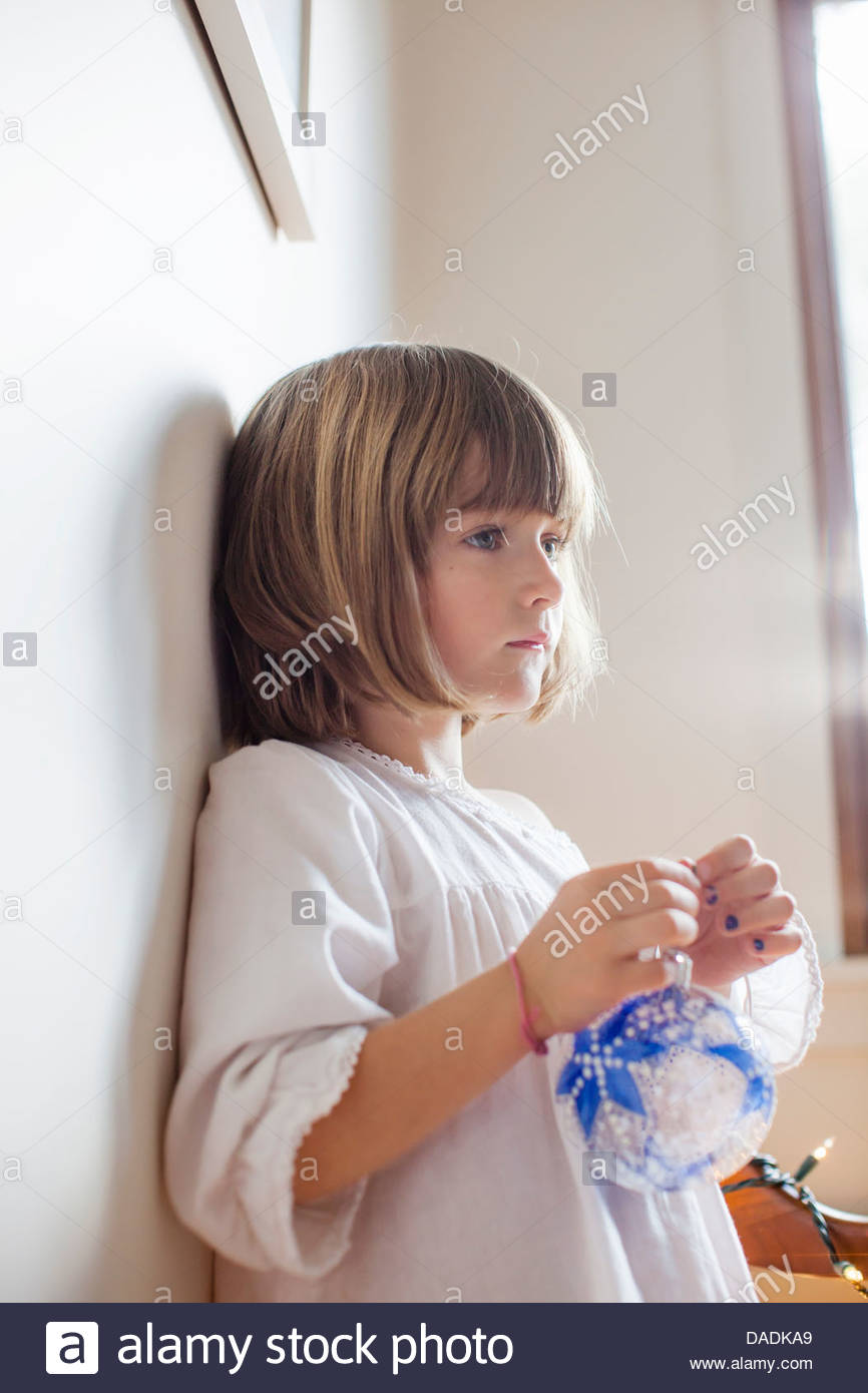 Child with blue bauble day dreaming - Stock Image