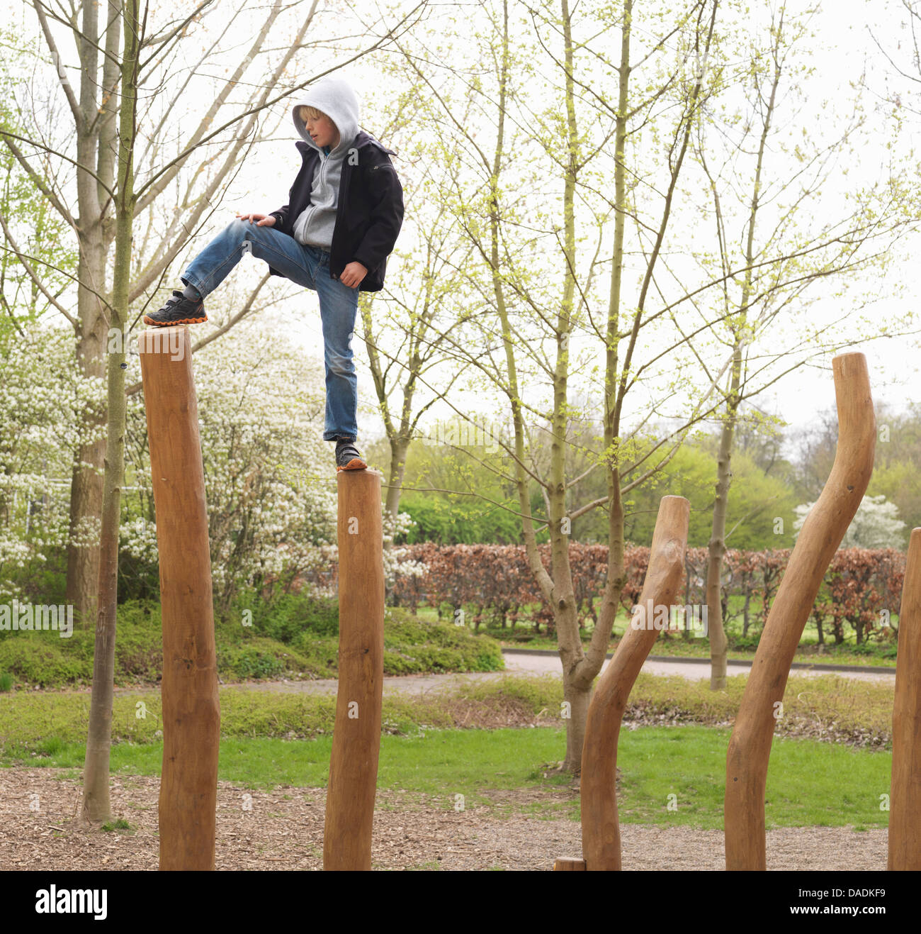 Boy stepping on wooden posts in park - Stock Image