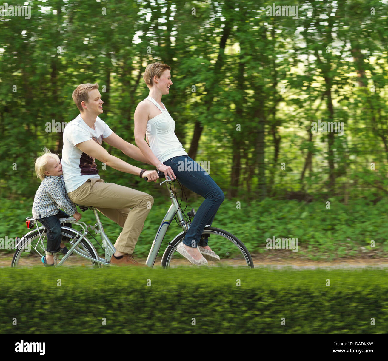Family with one child riding on bicycle together - Stock Image