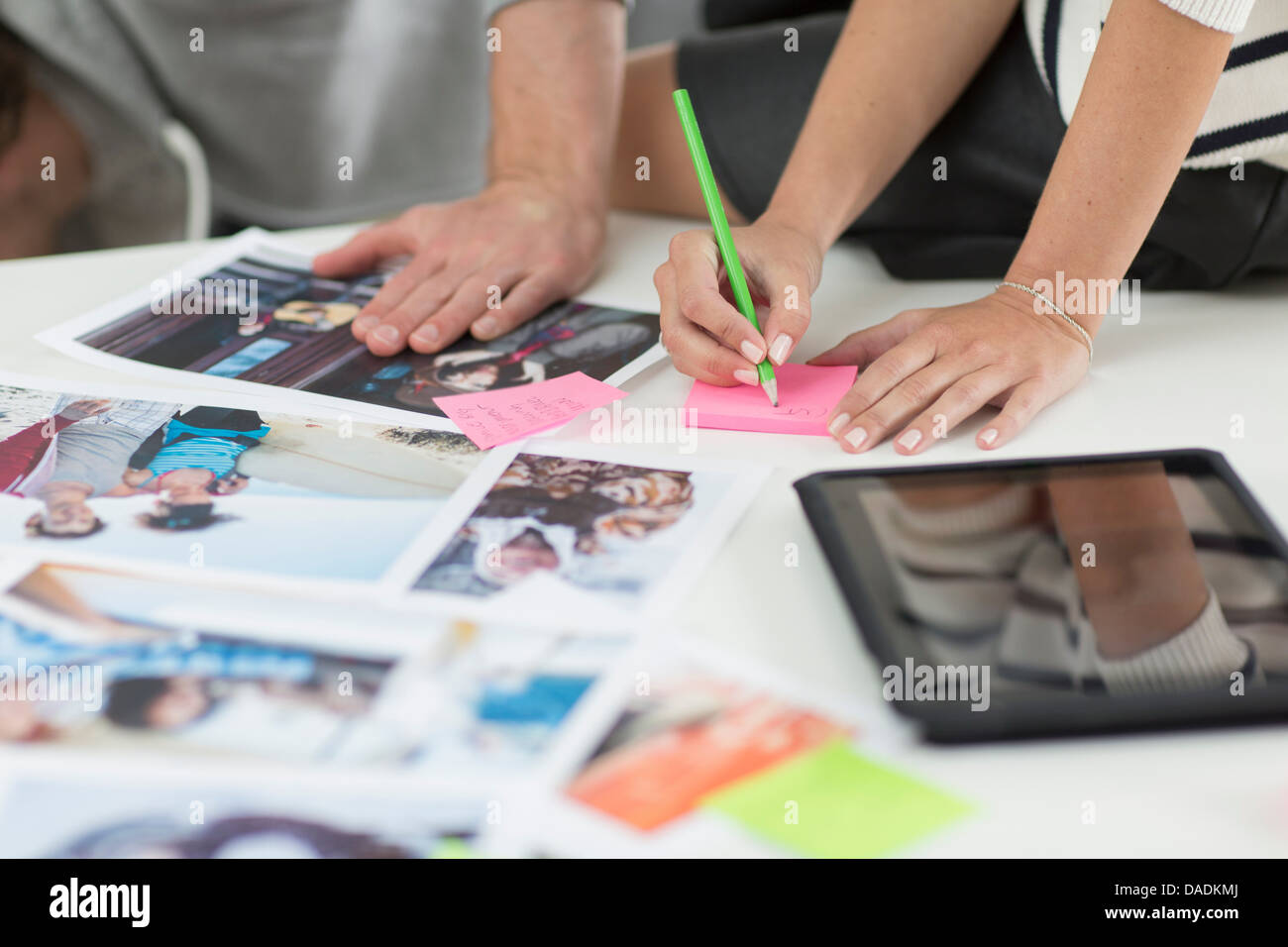Colleagues making notes on desk of photographs and digital tablet in creative office - Stock Image