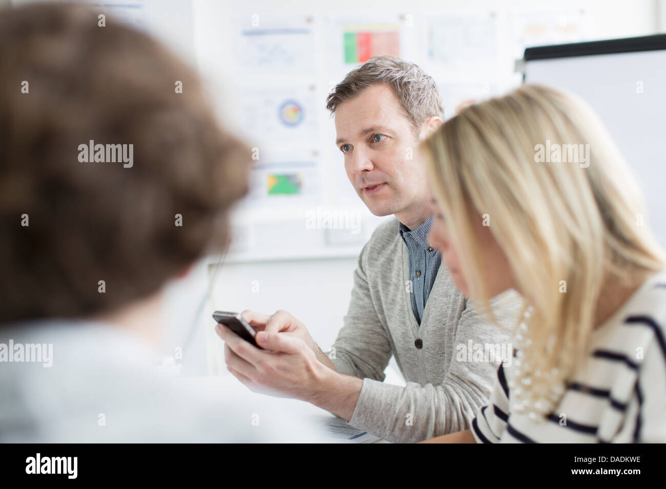 Mature man using mobile phone with colleagues in meeting in creative office Stock Photo