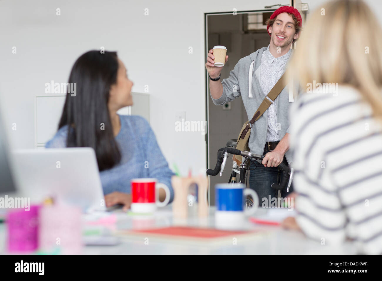 Young man arriving at meeting in creative office - Stock Image