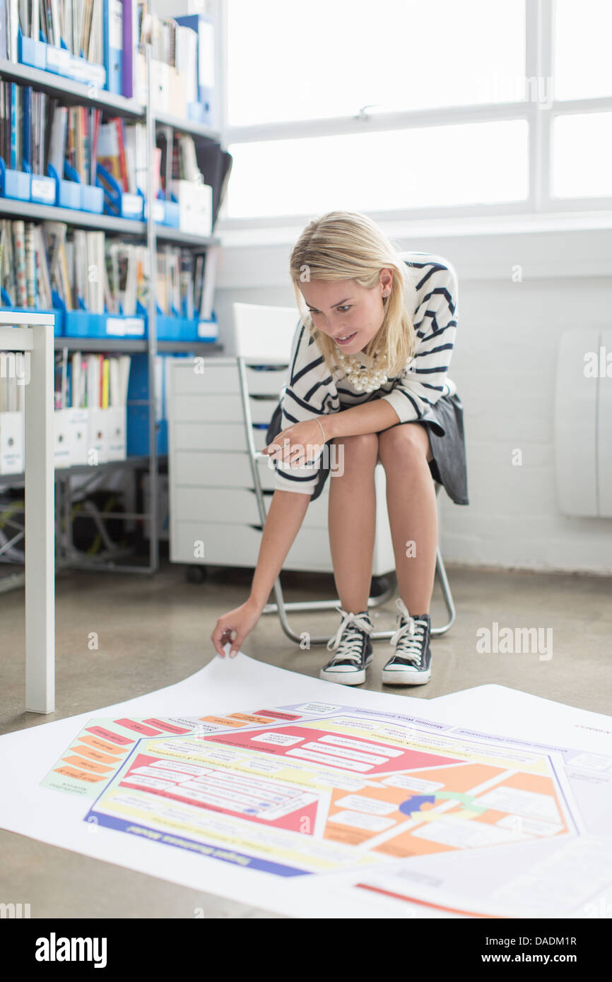 Young office worker looking at plans on floor in creative office - Stock Image