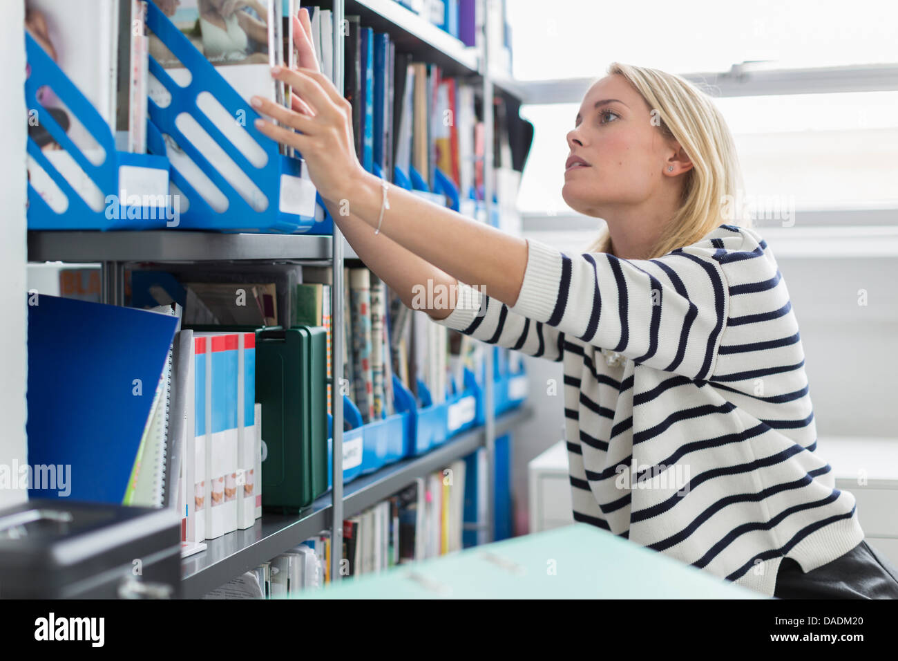 Young office workers reaching for books in office - Stock Image