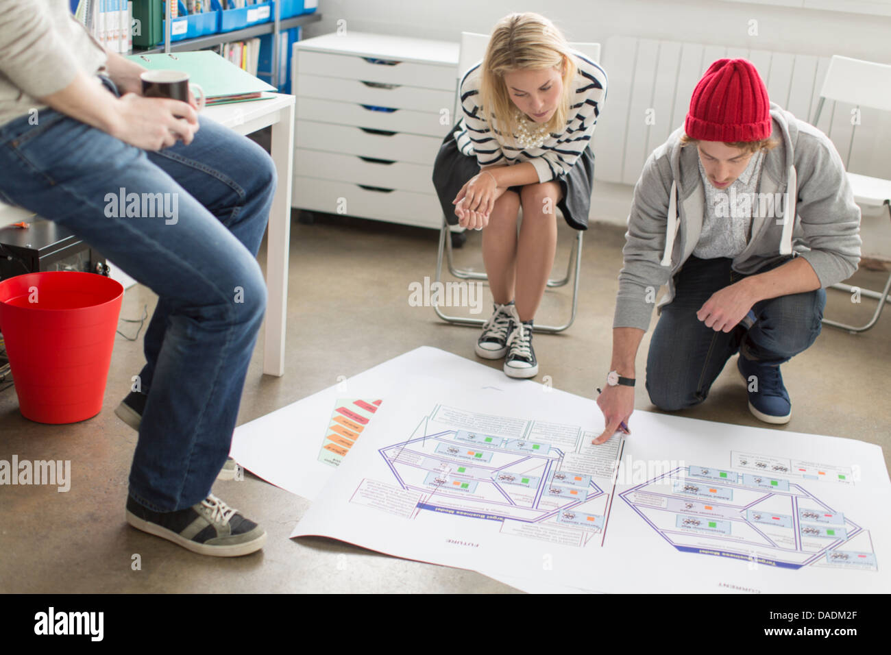 Young office workers discussing plans in creative office - Stock Image