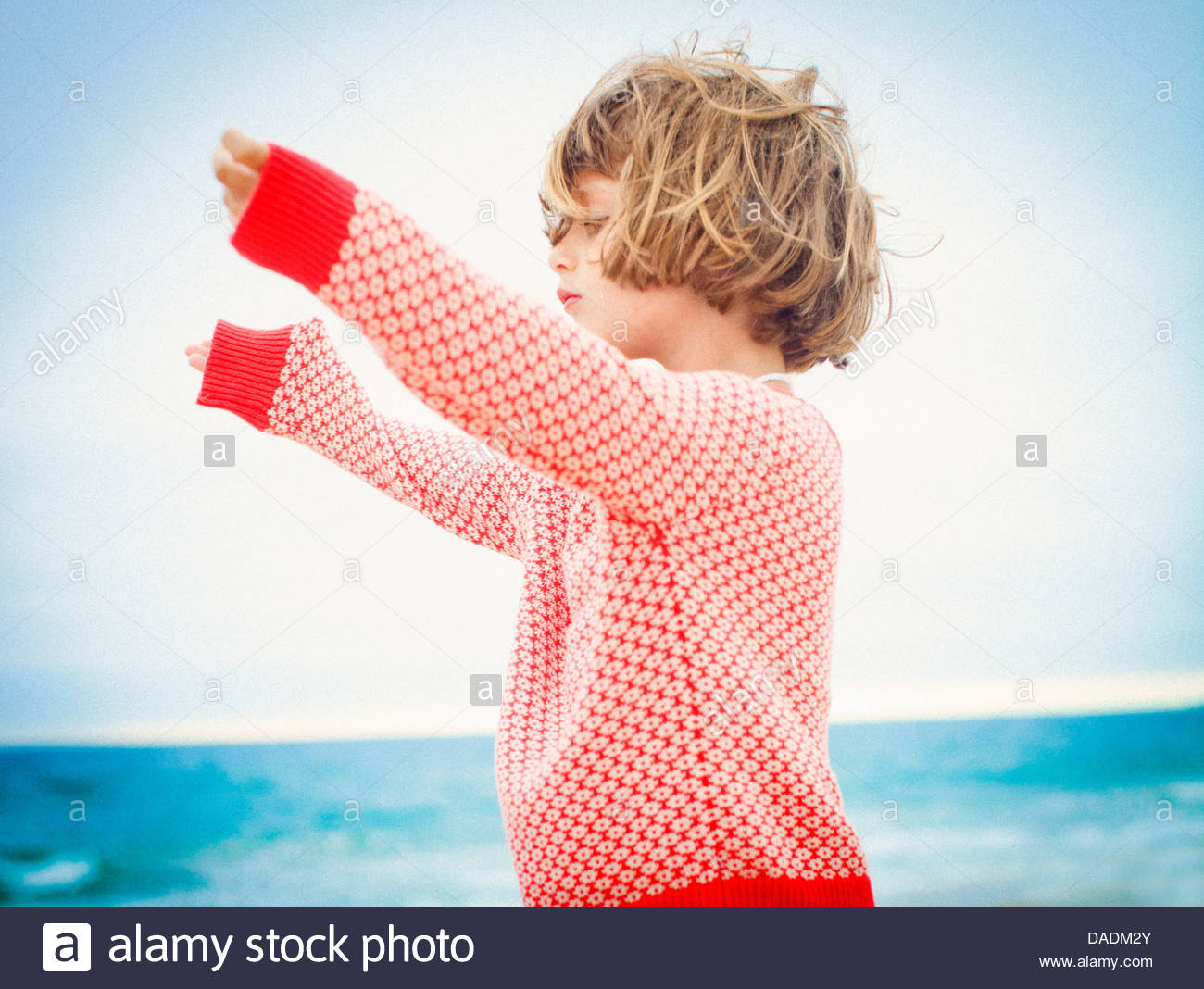 Child girl with outstretched arms enjoying the breeze - Stock Image