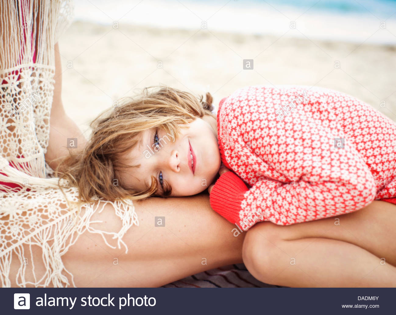 Child looking at camera resting head on mother's thigh - Stock Image