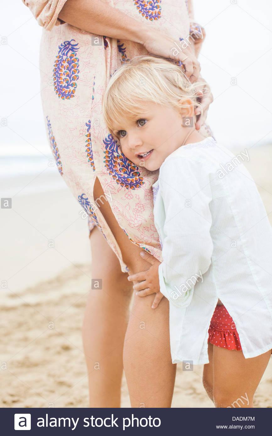 Girl hugging mother's leg - Stock Image