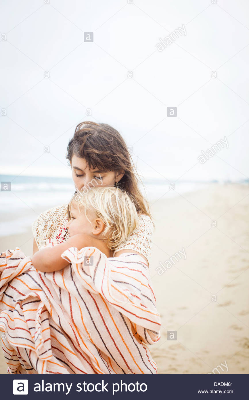 Mother cuddling child wrapped in towel - Stock Image
