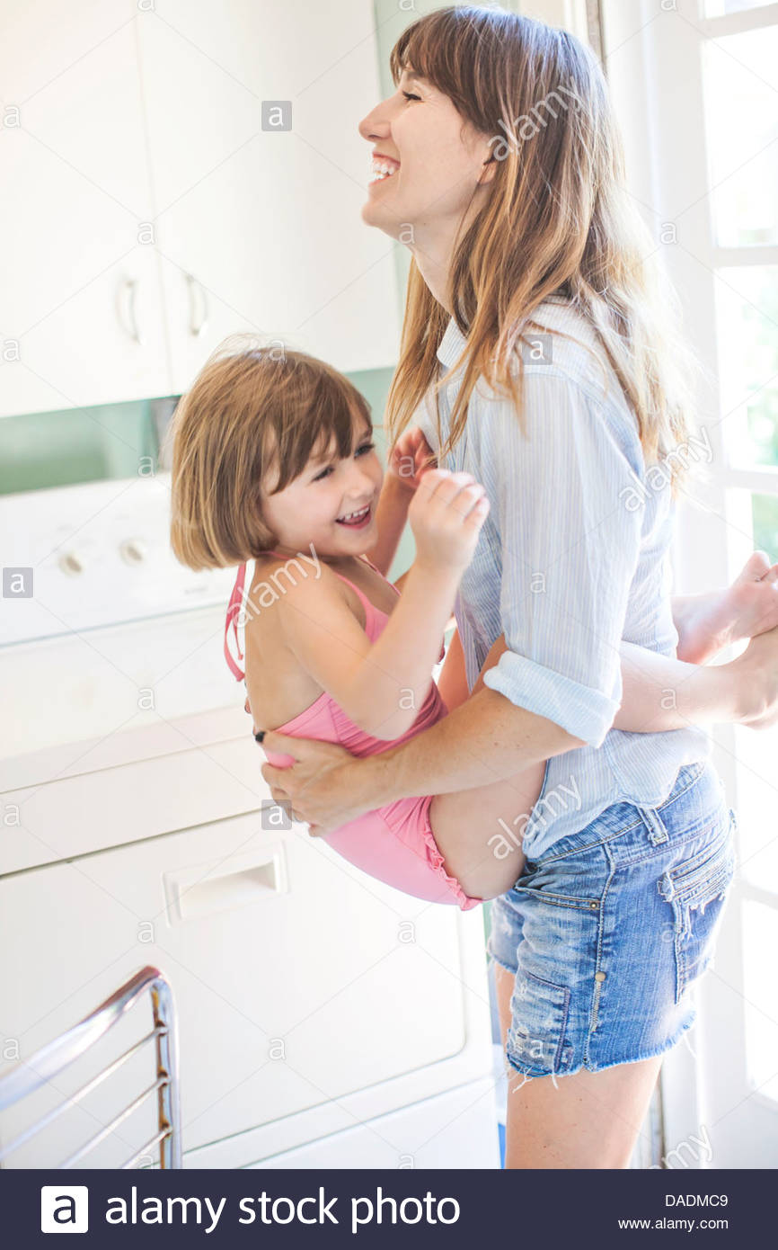 Mother carrying daughter in utility room, portrait - Stock Image