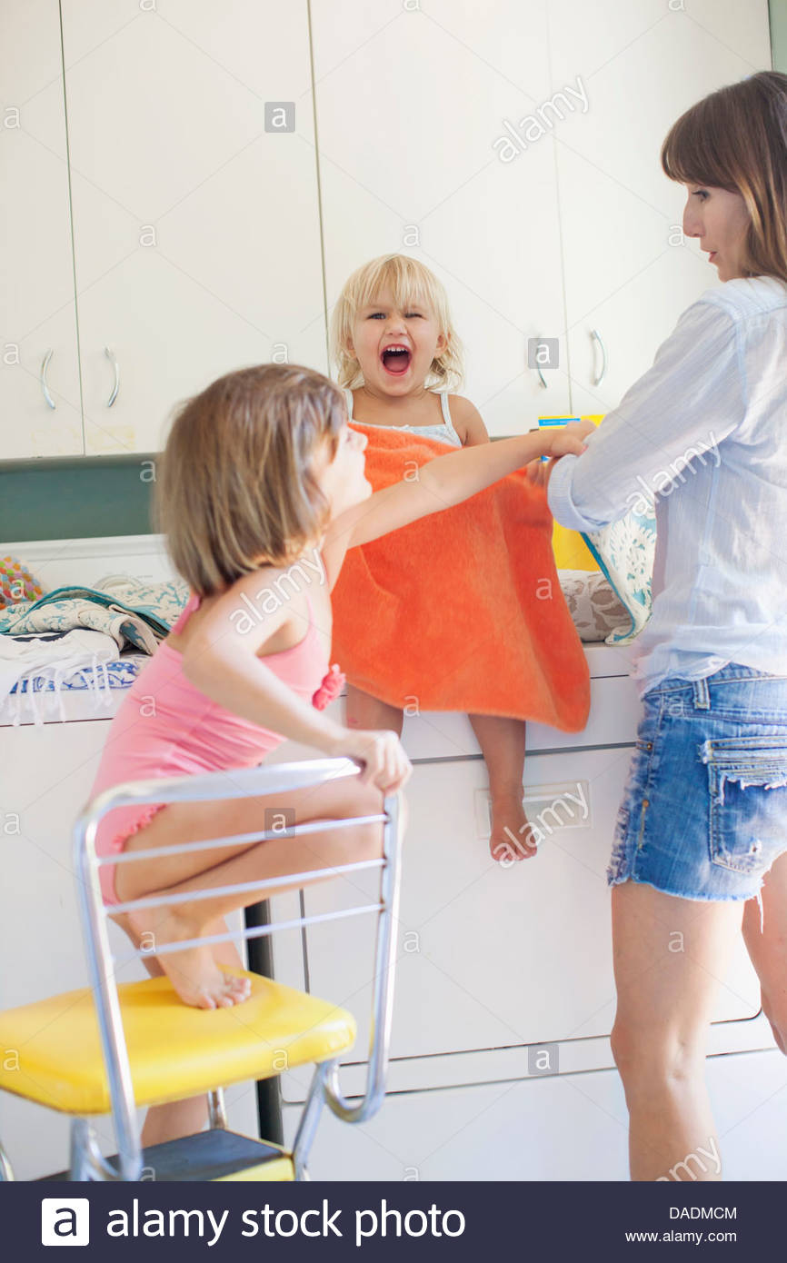 Mother and daughters in utility room - Stock Image