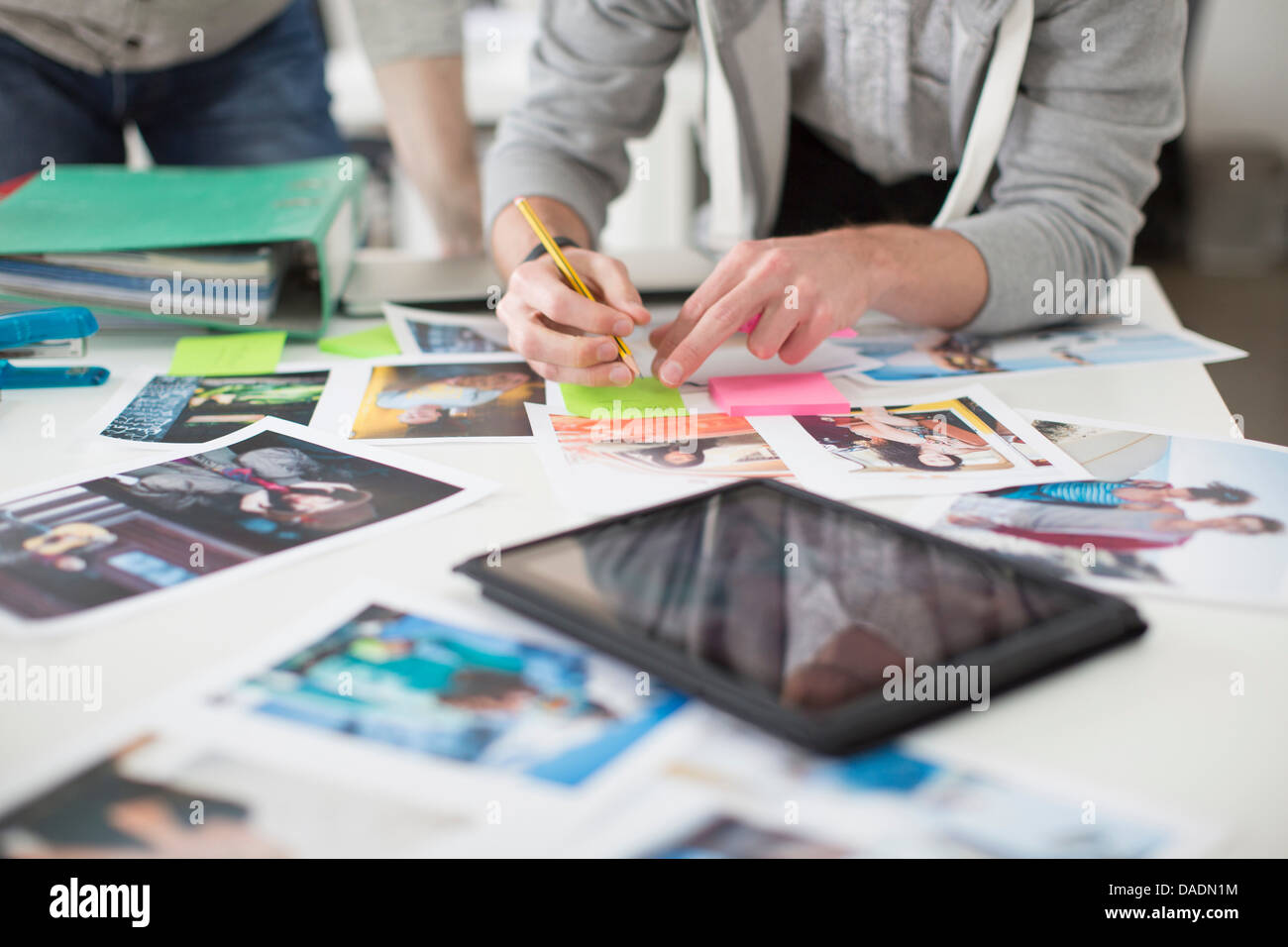 Young man making notes on desk of photographs with digital tablet in creative office - Stock Image