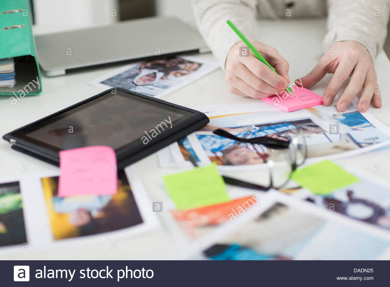 Man making notes on desk with digital tablet and photographs - Stock Image