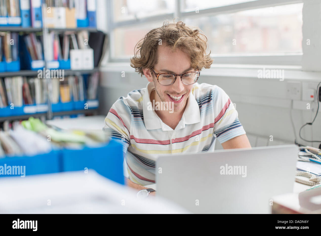 Young man using laptop and smiling in creative office - Stock Image
