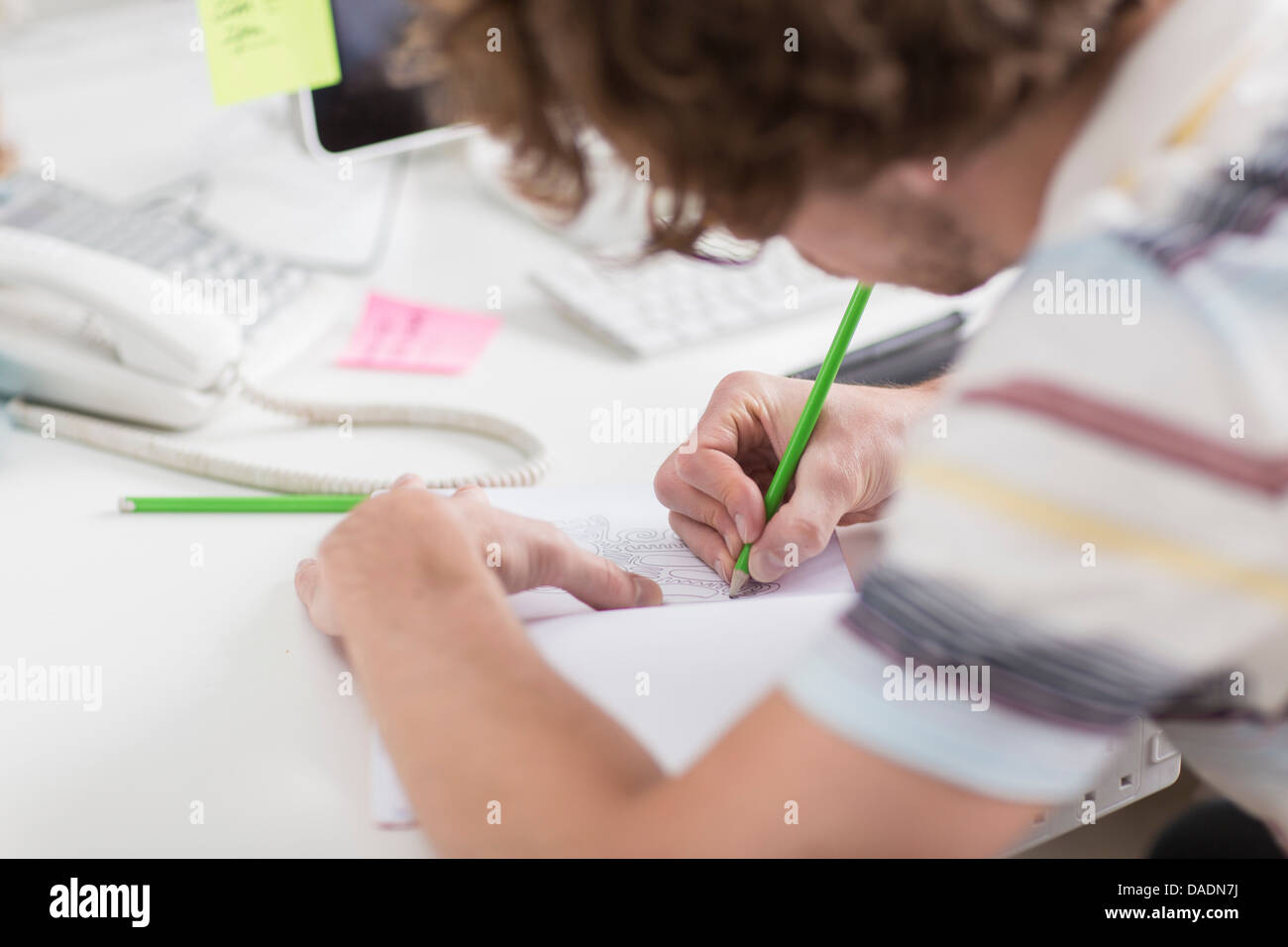 Young creative drawing plans at desk, close up - Stock Image