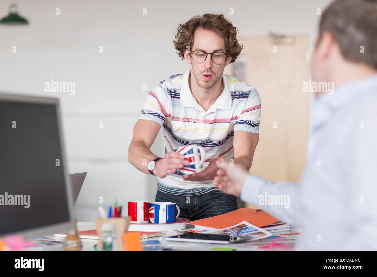 Office worker passing cup to colleague at desk - Stock Image
