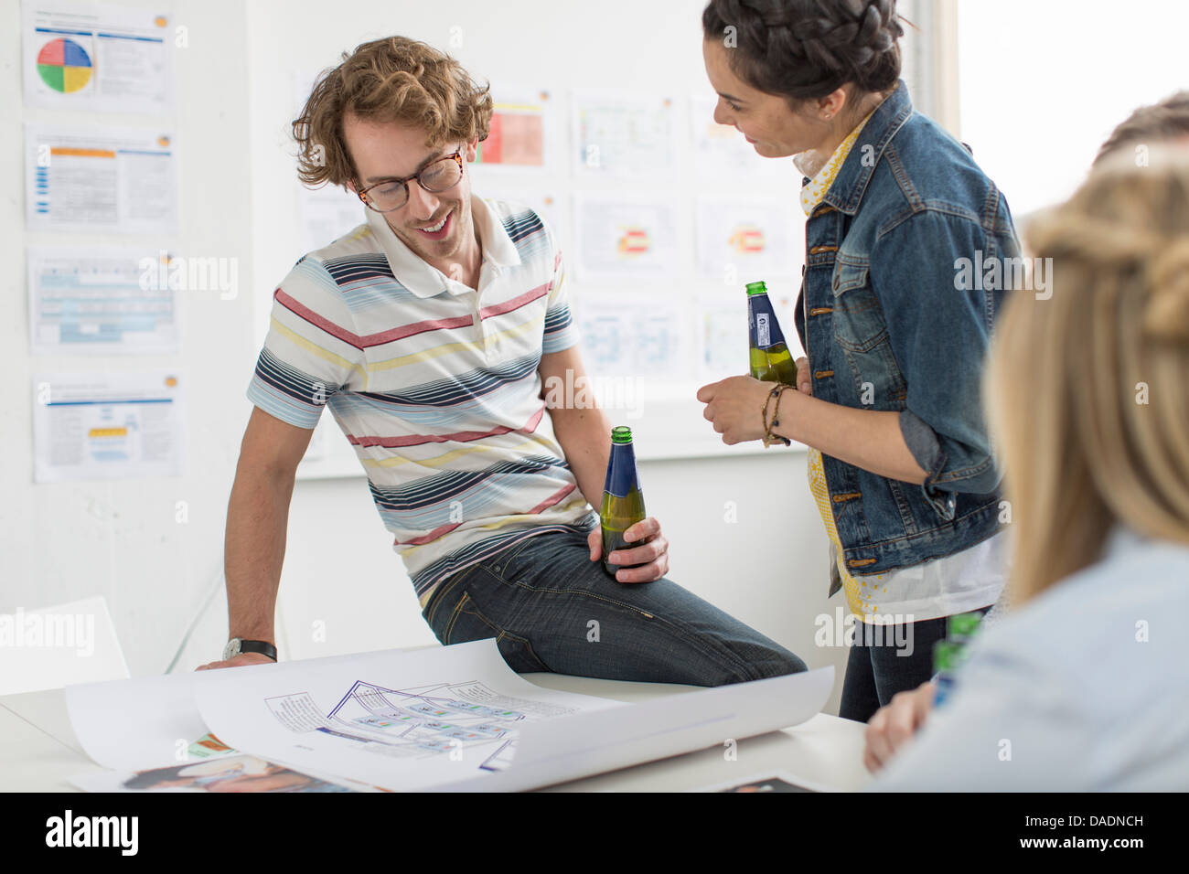 Office colleagues discussing creative plans on desk - Stock Image