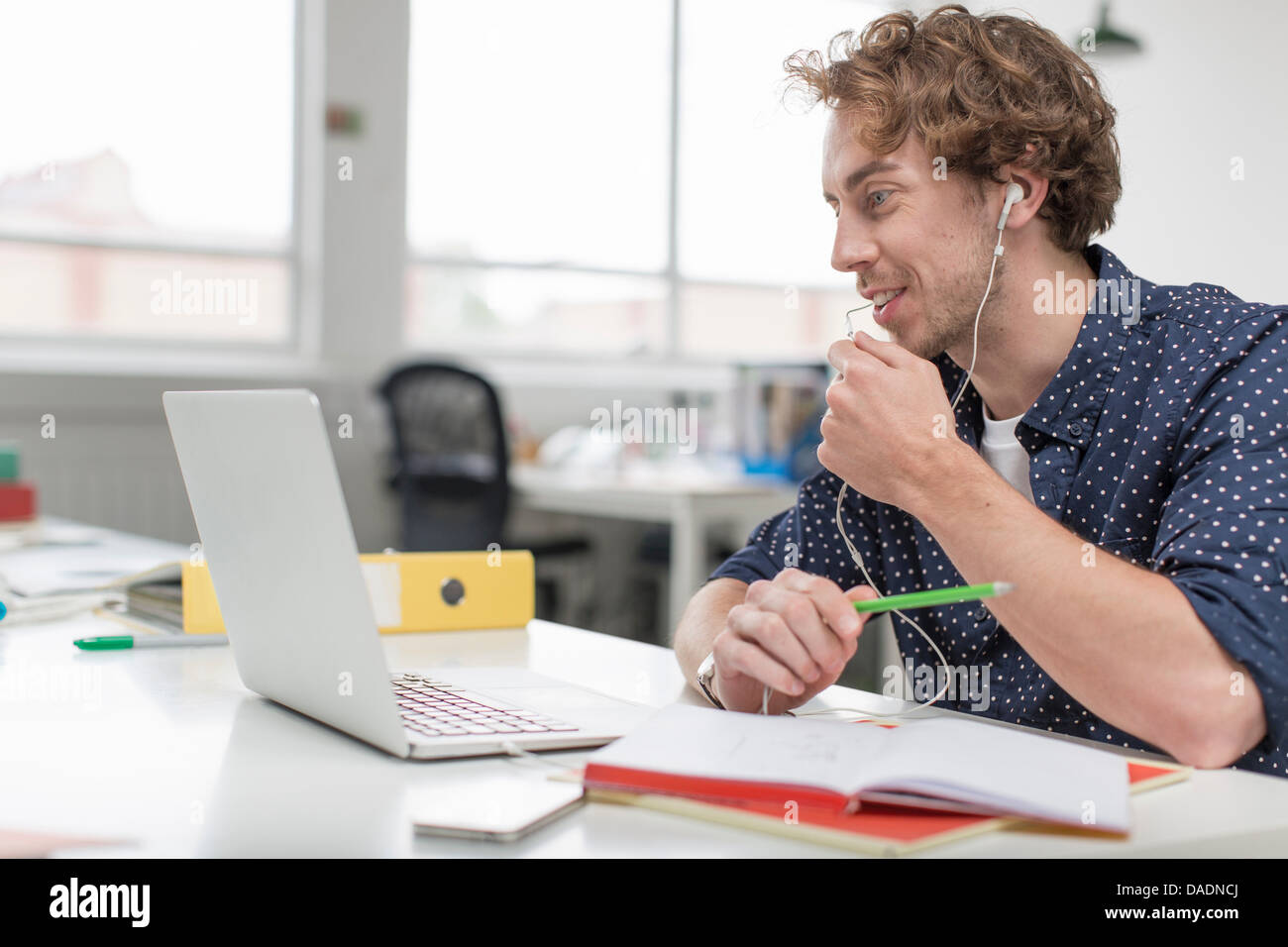 Young office worker using laptop and earphones at desk - Stock Image