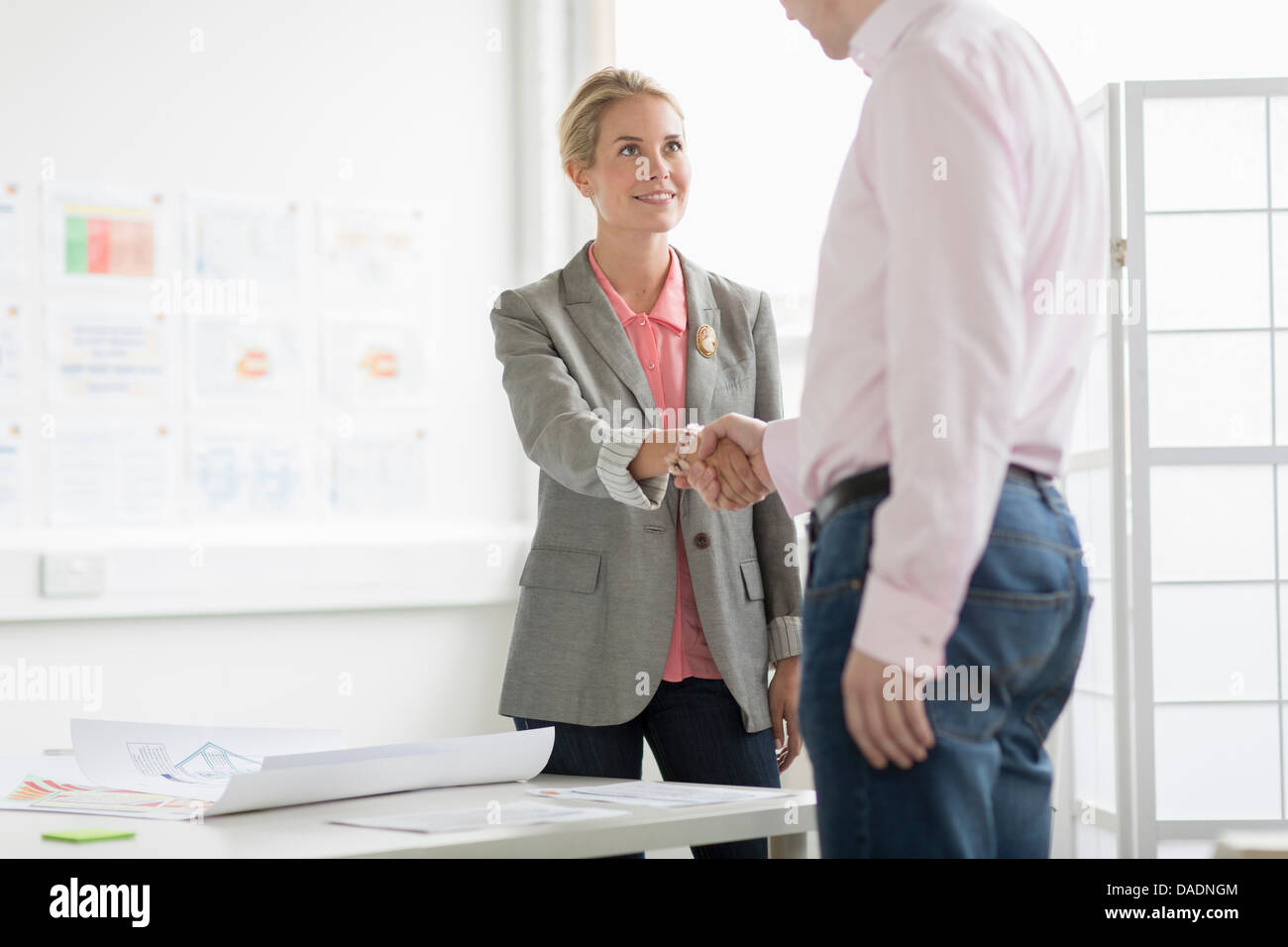 Businesswoman shaking hands with man in office - Stock Image