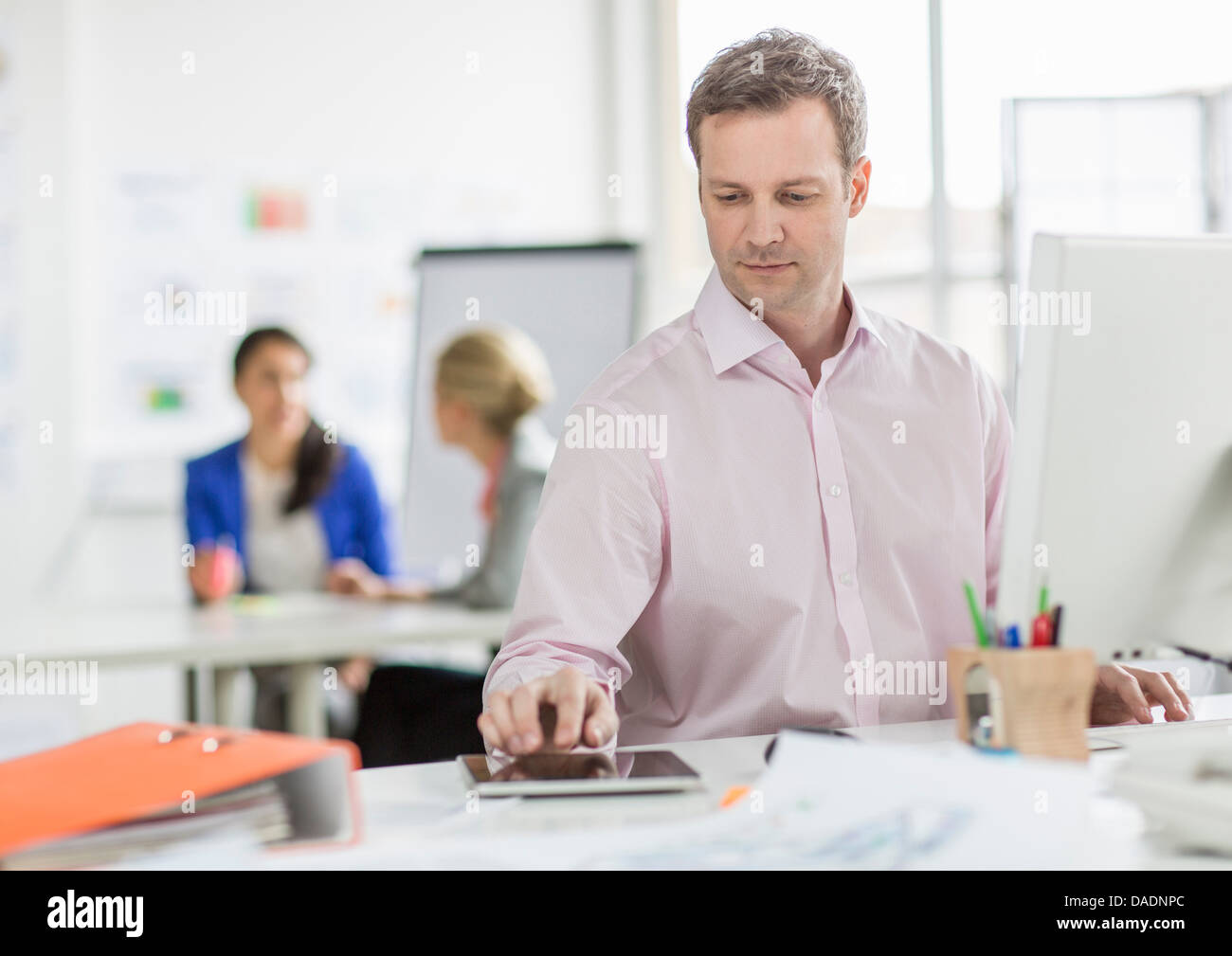 Mature businessman using digital tablet at desk in office - Stock Image