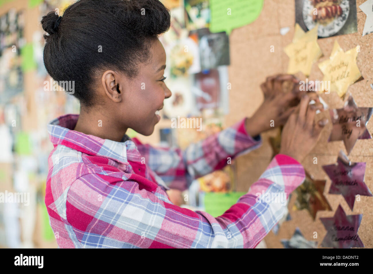 Young woman pinning things to noticeboard - Stock Image