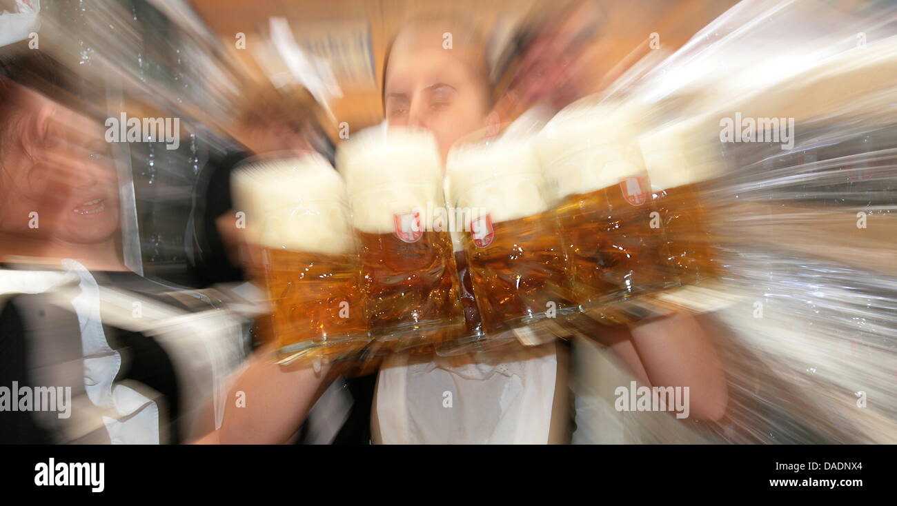 FILE - The archive illustration dated 22 September 2007 shows a waitress serving beer mugs at the 174th Oktoberfest - Stock Image