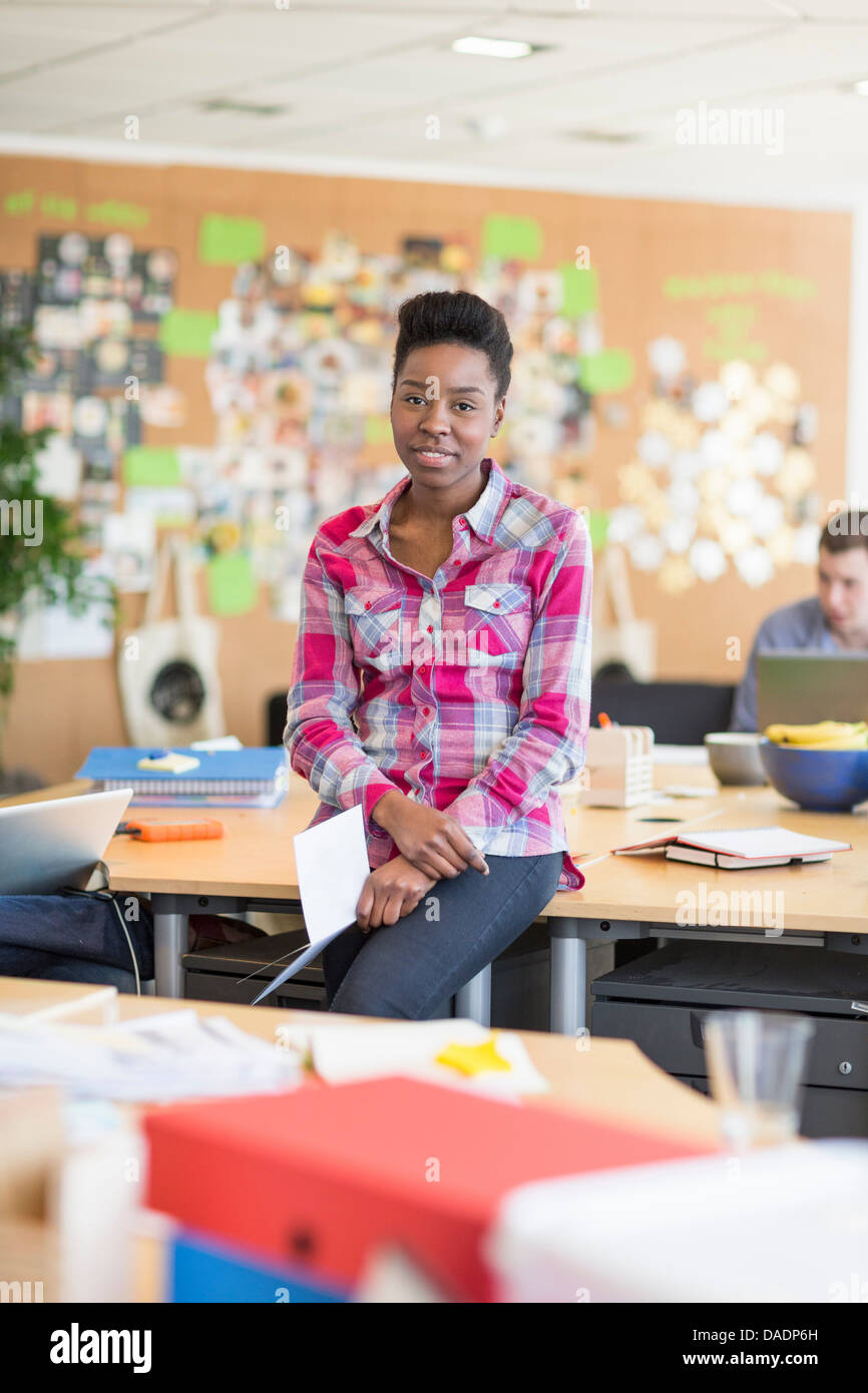 Young woman in creative office, portrait - Stock Image