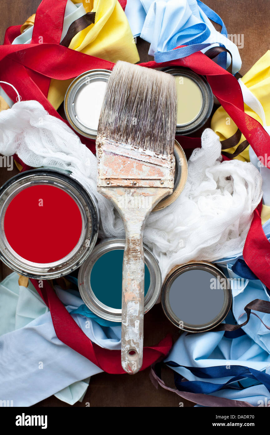Still life of paint brush, paint tins and textiles - Stock Image