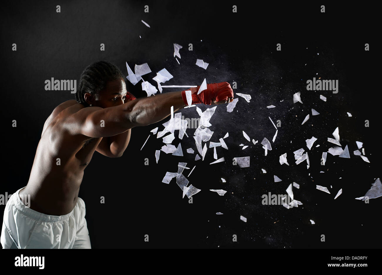 Young boxer punching through shattered glass - Stock Image