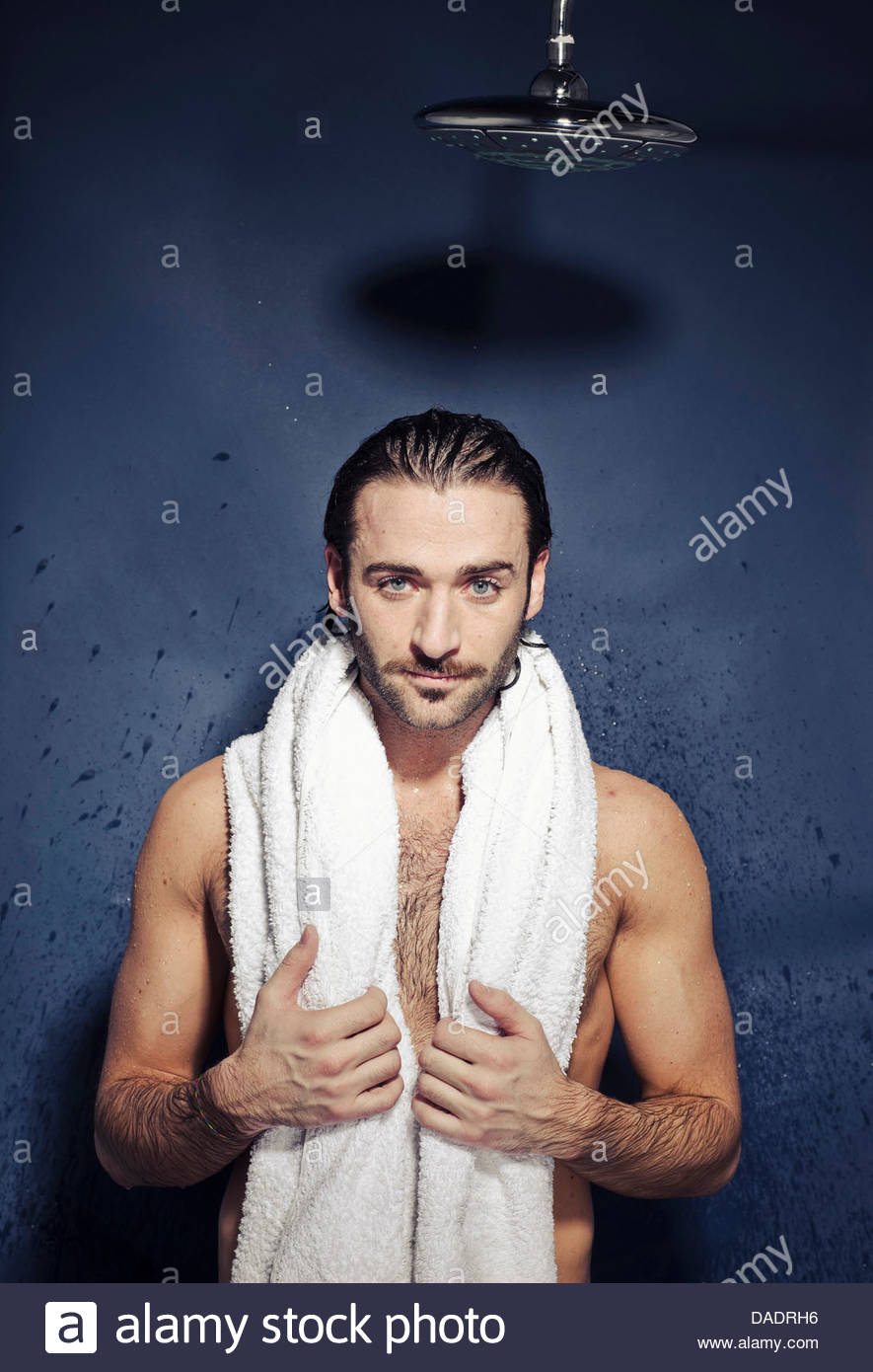 Young man after shower with towel around shoulders - Stock Image