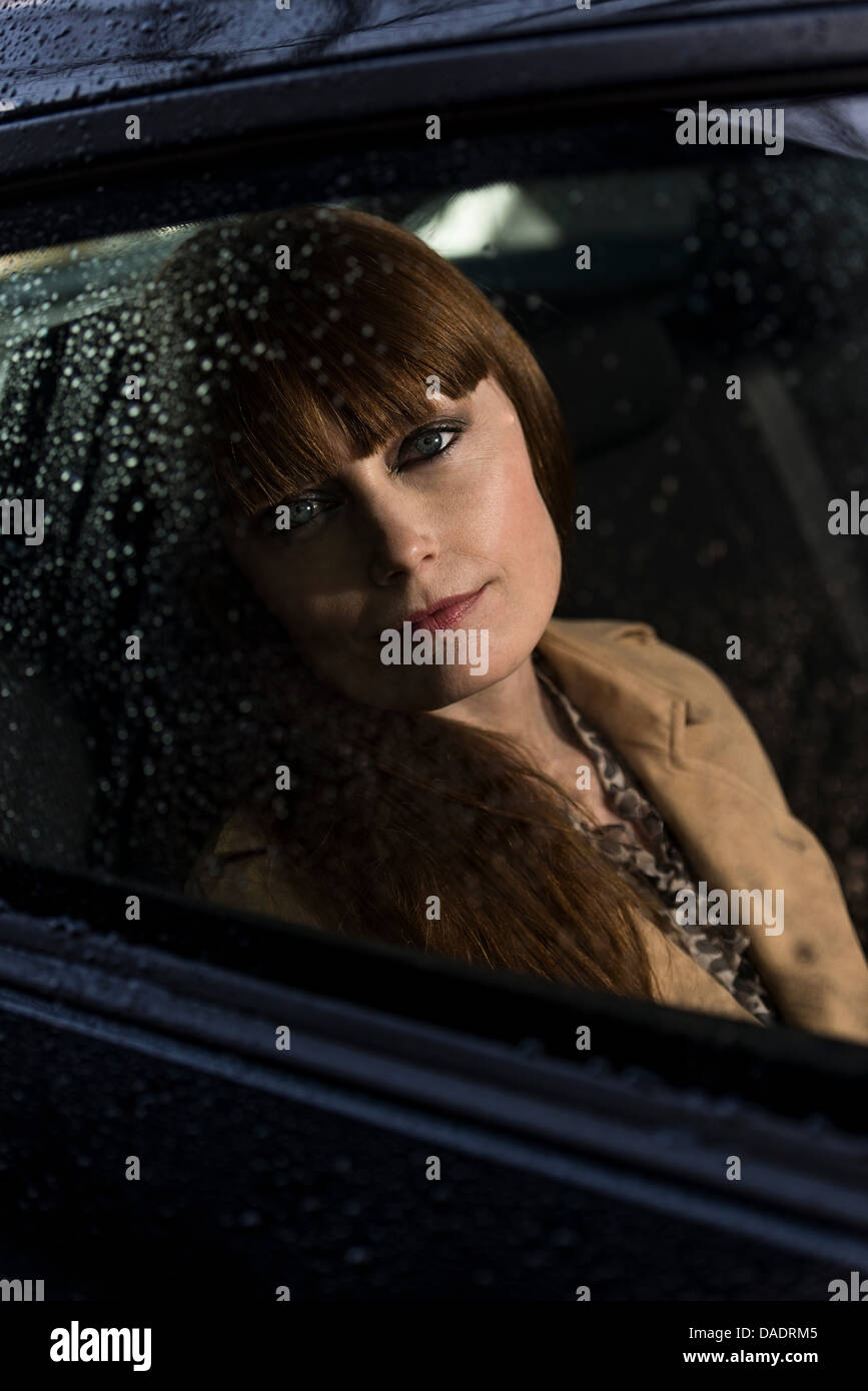 Business woman looking out of car window - Stock Image