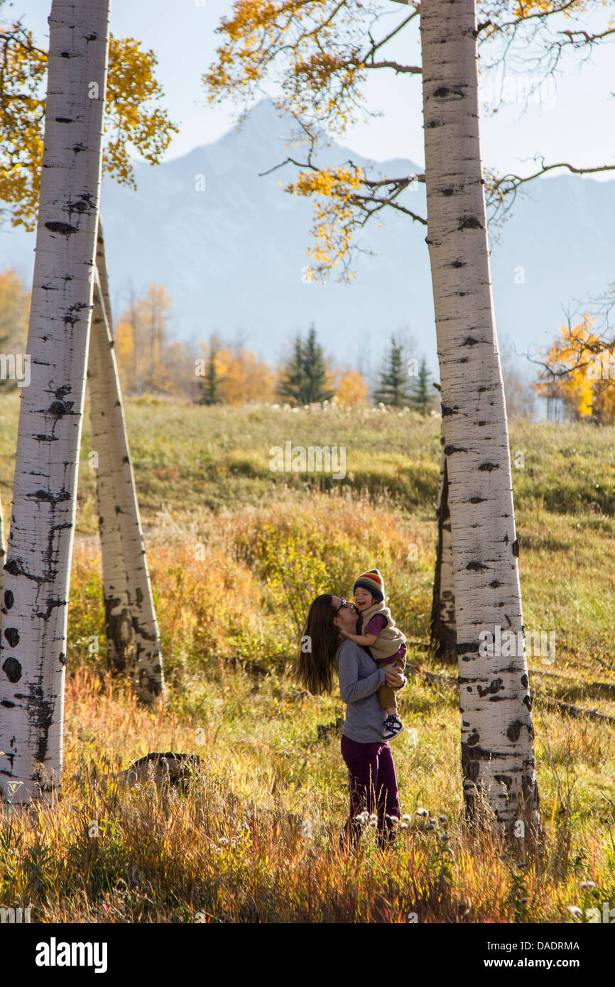 Mother holding toddler amongst silver birch trees - Stock Image
