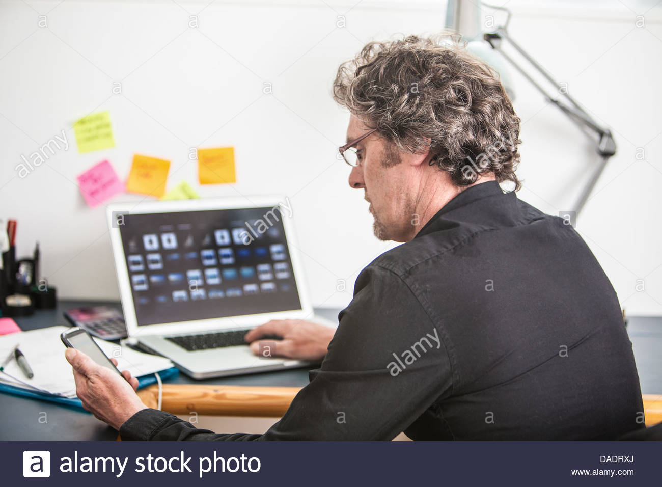 Man looking at smartphone screen in his office - Stock Image