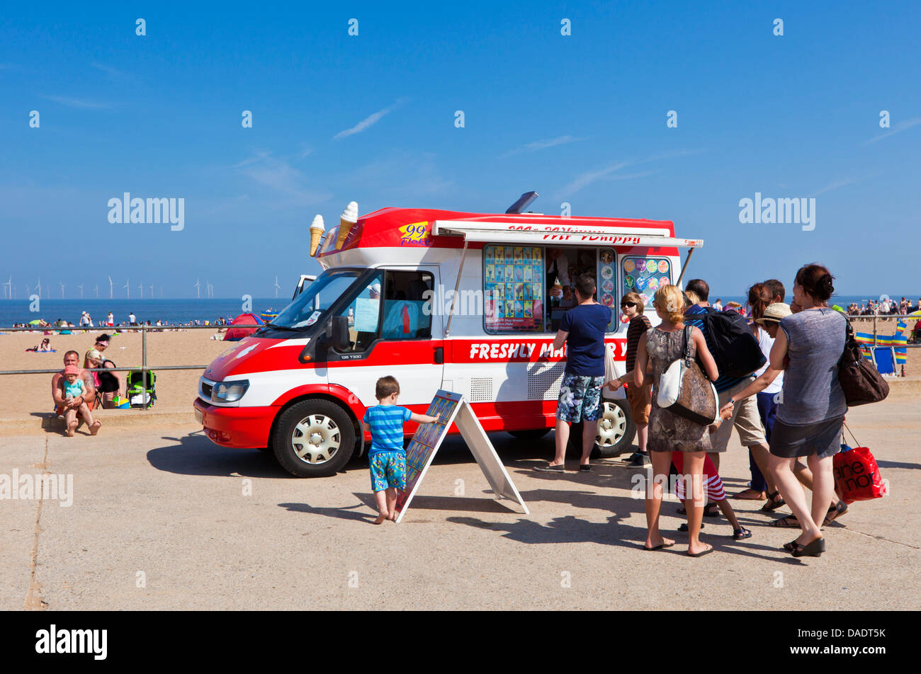 People queueing for an ice cream from an ice cream van parked on Skegness beach promenade Lincolnshire England UK Stock Photo