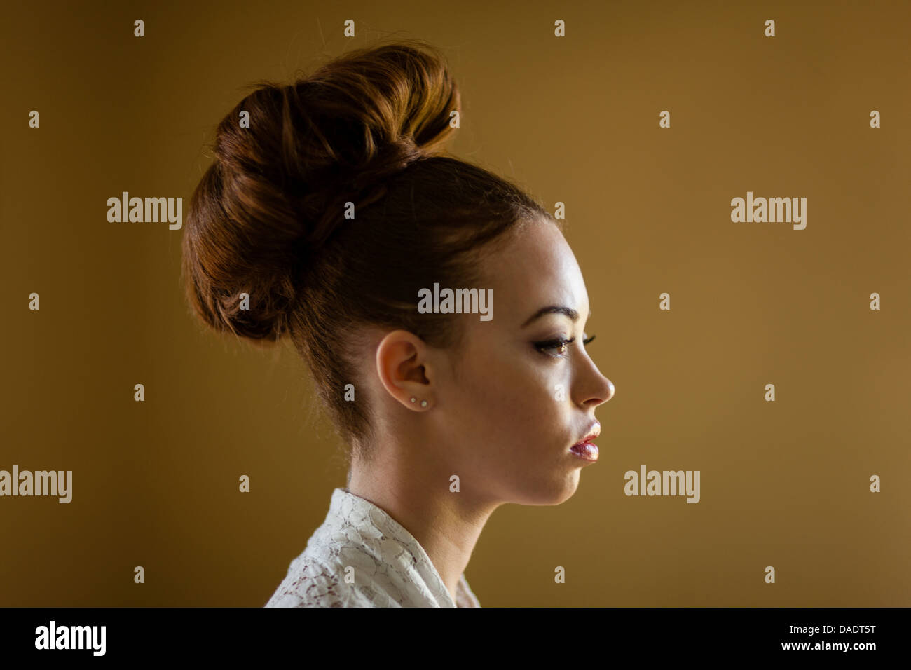 Close up portrait of a young woman with her hair in a bun - Stock Image