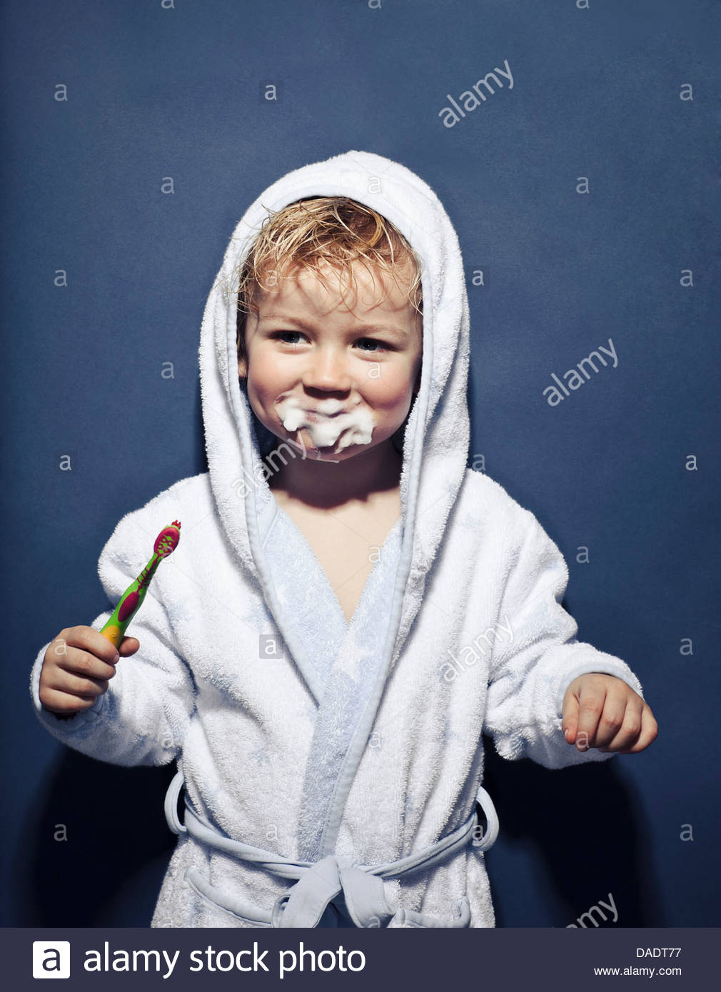 Young girl with frothy mouth holding toothbrush - Stock Image
