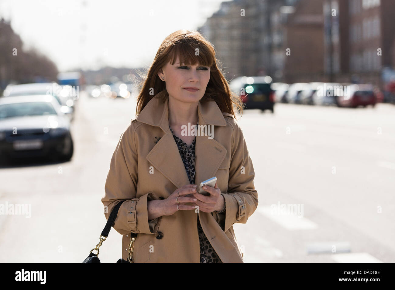 Woman with mobile phone walking down street - Stock Image