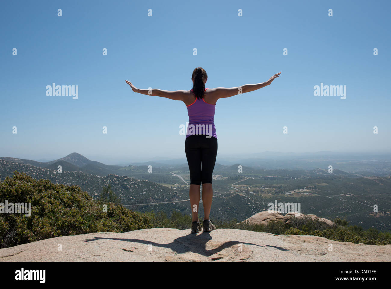 Woman with outstretched arms overlooking view of San Diego, California, USA - Stock Image